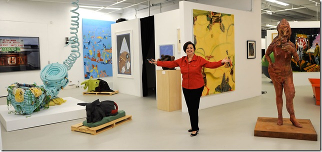 Elayne Mordes in Whitespace, surrounded by her art collection. At the far left rear is a photograph of the Odeon Theater by Hubbard and Birchler (a collaborative team of American/Swiss Teresa Hubbard (b. 1965) and Swiss Alexander Birchler (b. 1962). The center atrium to Elayne's left is devoted to the soft sculptures and paintings of Christian Holstad (b. 1972, American). Just behind Elayne is Green Land Distortion (2004), by American artist Alyson Shotz (b. 1964), and to the right is Suzy Wong (2006), a bronze sculpture by Jonathan Meese (b. 1970, Japan). (Photo by Katie Deits)