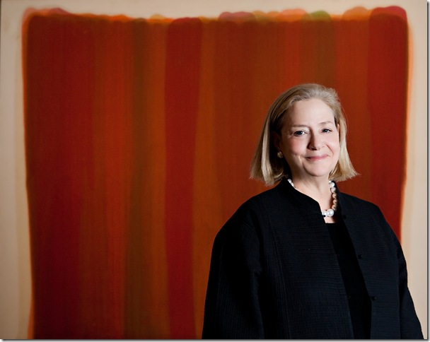 Hope Alswang stands in front of Autumnal (1959), by Morris Louis, a painting in the Norton collection.