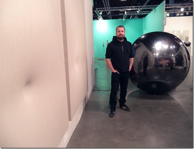 Sinisa Kukec with his sphere sculpture and two canvases. (Photo by Katie Deits)